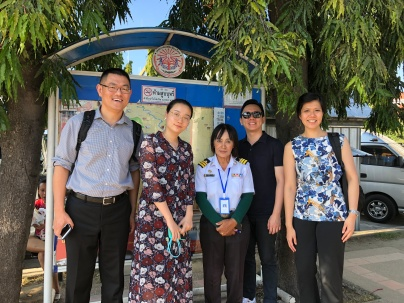 Project team members visiting a city bus stop. From left to right: Xu Kuang, Fu Yaqin, a local bus conductor, Saw Chun Kiat and Tan Lu Hsia.